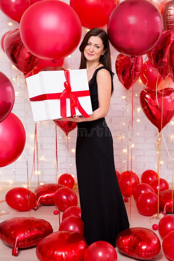 Valentine`s day concept - middle aged beautiful woman in long black dress with big gift box and red balloons royalty free stock photos