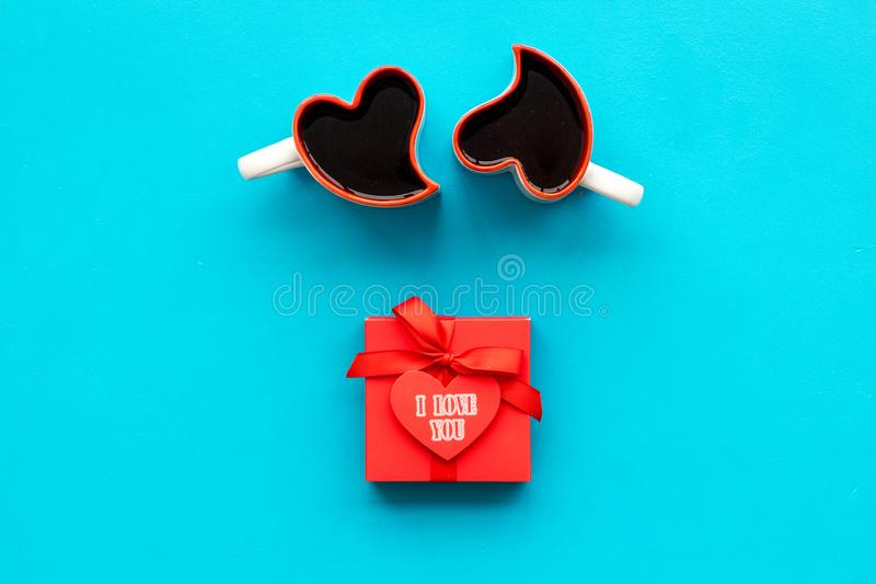 Valentine`s day concept. Red gift box, heart-shaped mugs on blue background top view copy space stock image