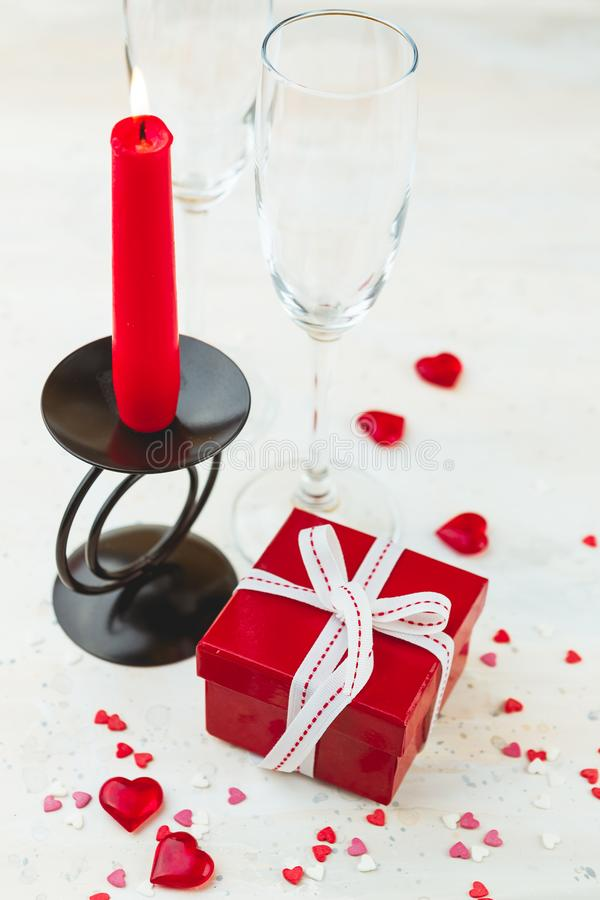 Valentine's day concept. Red gift box with white ribbon, wine glass, red candle and hearts jn light background royalty free stock images