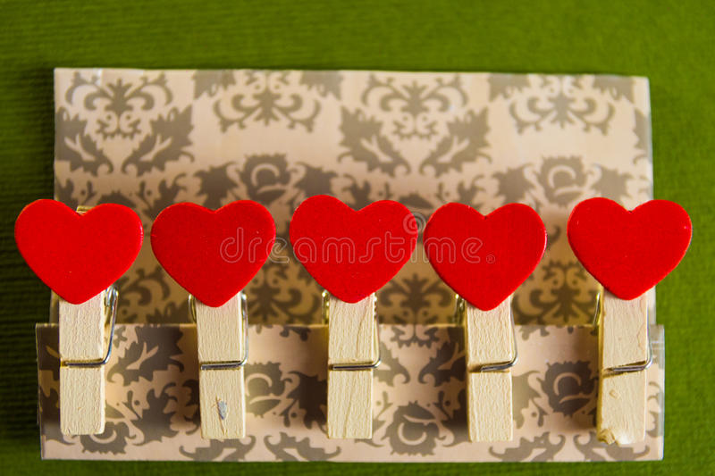 Valentine`s day concept. Red heart shape clothespins fixed on a cardboard with textured green background. stock image