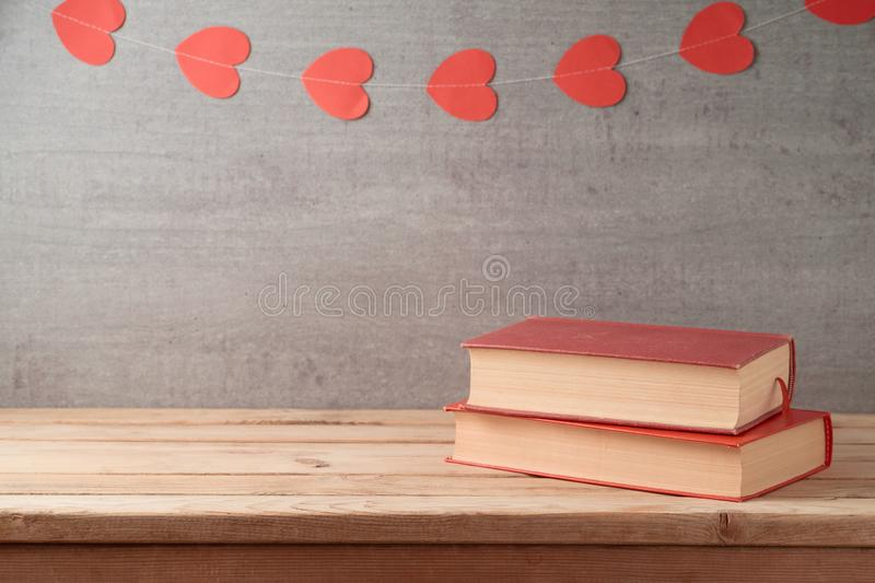 Valentine`s day concept with romantic books on wooden table over garland stock images