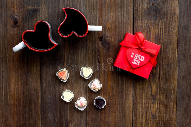 Valentine`s day concept. Sweets, red gift box, heart-shaped mugs on dark wooden background top view stock photography