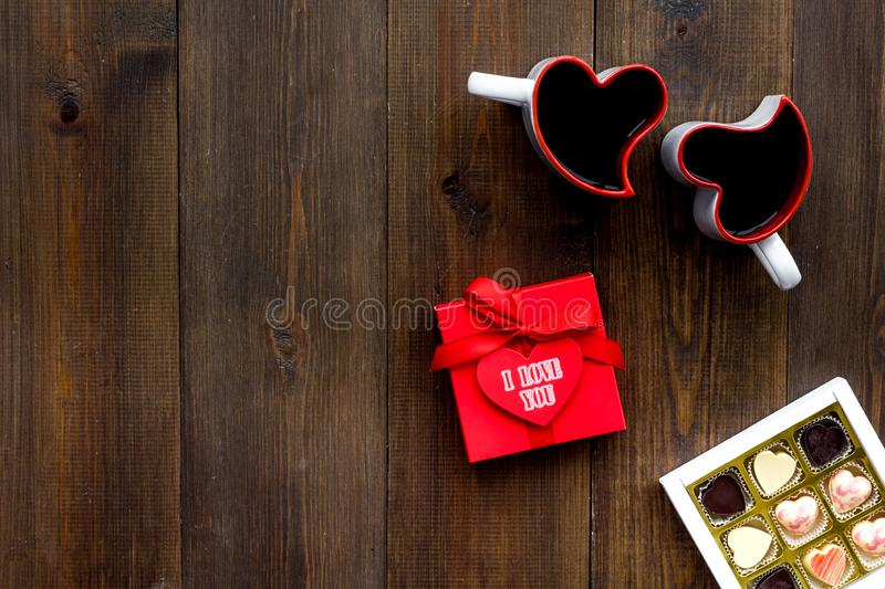 Valentine`s day concept. Sweets, red gift box, heart-shaped mugs on dark wooden background top view space for text royalty free stock photography