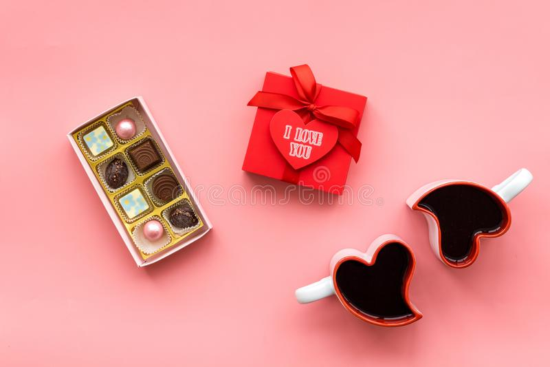 Valentine`s day concept. Sweets, red gift box, heart-shaped mugs on pink background top view stock photos
