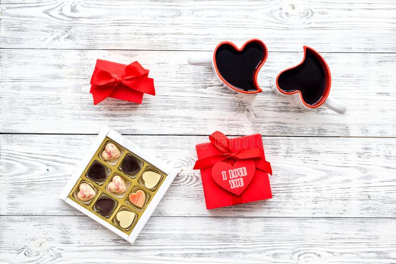 Valentine`s day concept. Sweets, red gift box, heart-shaped mugs on white wooden background top view space for text stock photos