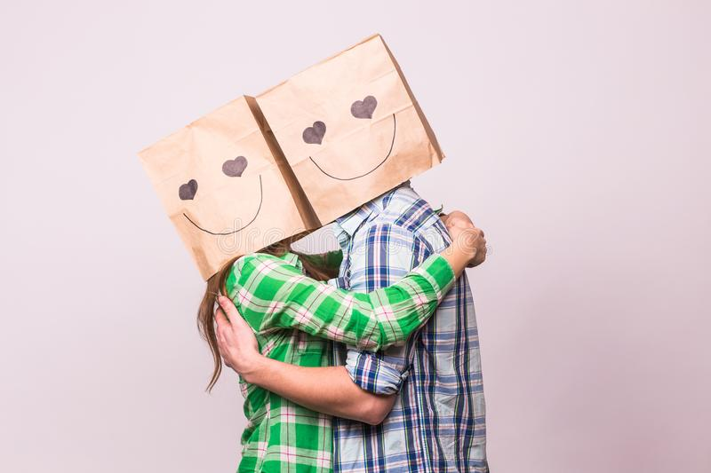 Valentine`s day concept - Young love couple with bags over heads on white background royalty free stock image
