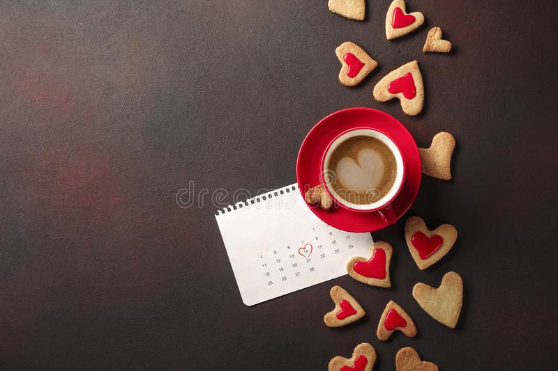 Valentine`s Day with a cup of coffee, a heart-shaped cookie and a calendar stock photo