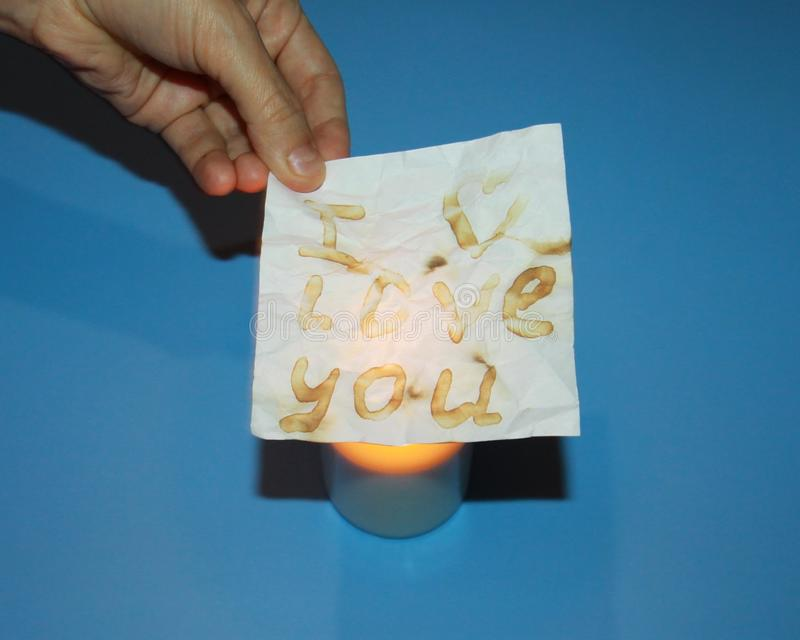 Valentines day declaration of love a piece of paper with the inscription i love you and a burning candle stock images