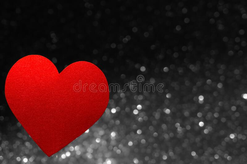 Valentine`s Day decoration. Red heart shape isolated on blurred gray lights. Love background stock photos