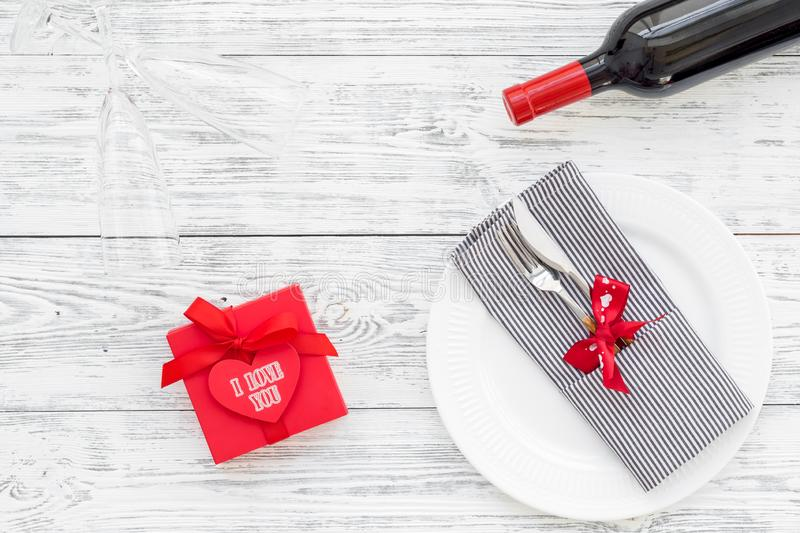 Valentine`s day dinner concept. Decorated dishes, tableware, wine, gift box on white wooden background top view copy stock images