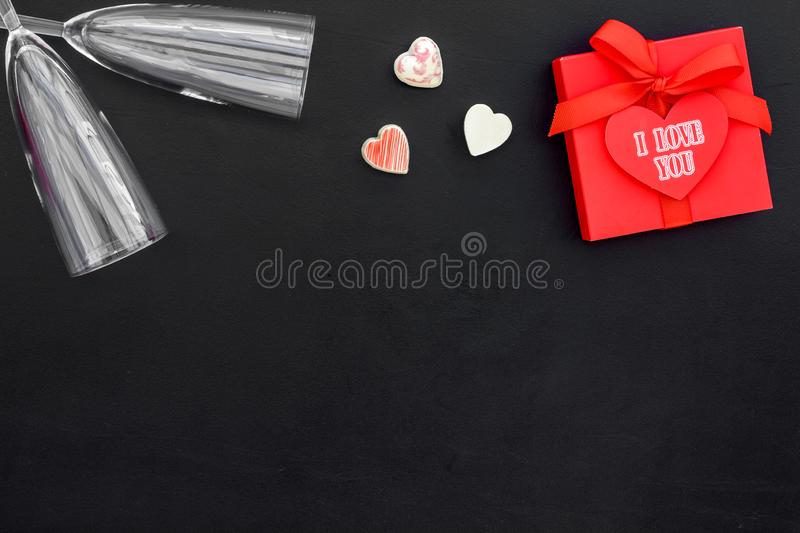 Valentine`s day dinner concept. Wine glass and gift box on black background top view copy space stock photography
