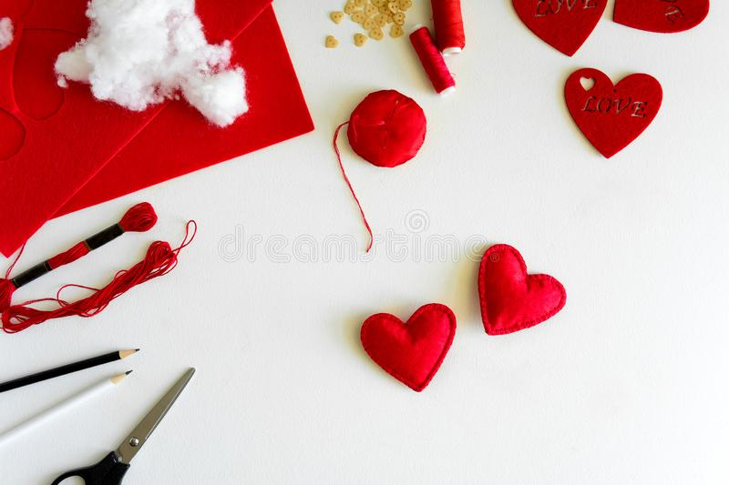 Valentine`s day felt crafts. Woman hands sewing red hearts. DIY. Flat lay. Top view royalty free stock photo