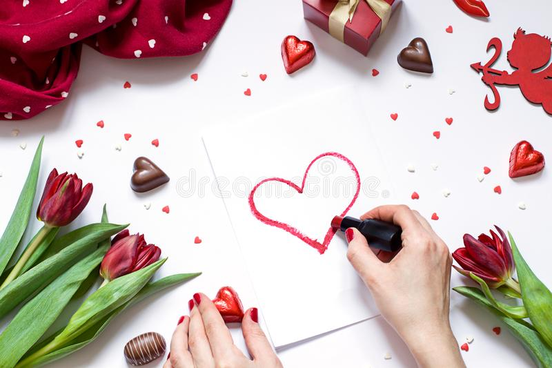 Valentine`s day flat lay. Woman`s hands drawing a heart with red lipstick. Romantic concept composition with flowers and cupid. royalty free stock image