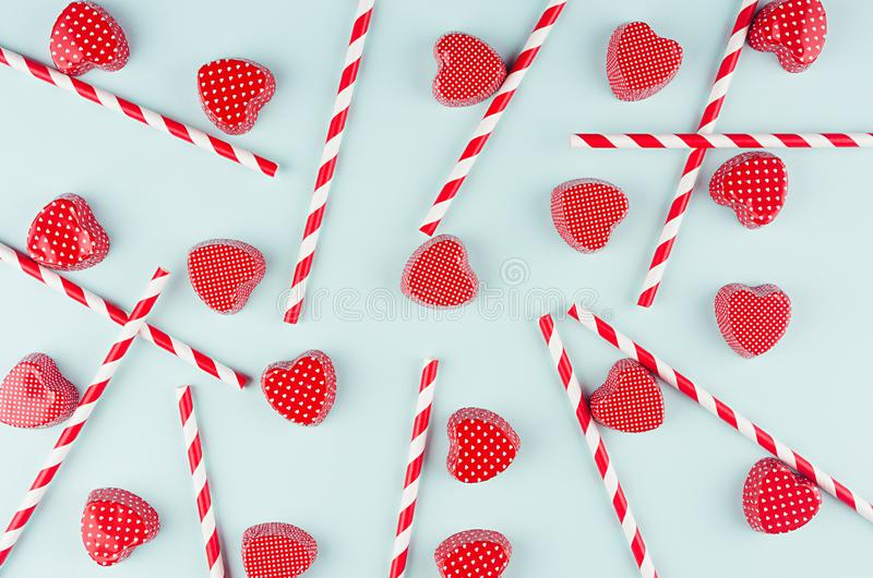 Valentine`s day funny background - red candy hearts and striped cocktail straws on light mint background as decorative pattern. Valentine`s day funny background stock image
