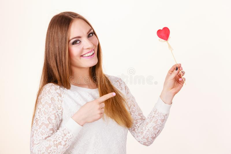 Beautiful woman holding heart shaped hand stick stock photo
