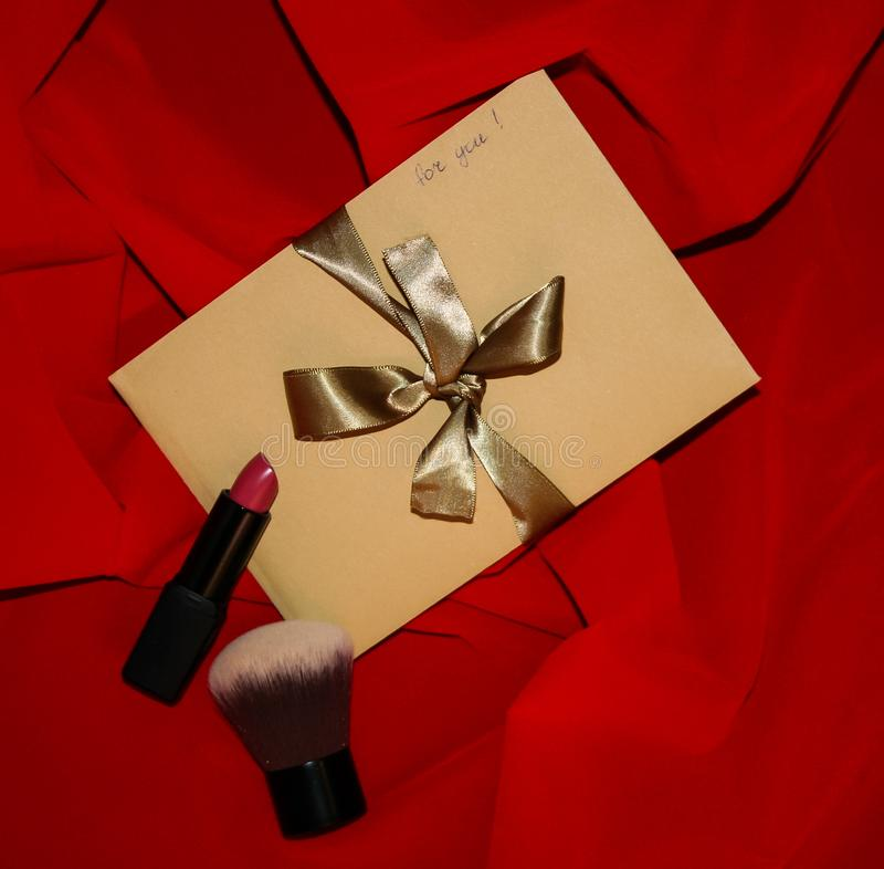 Valentine`s Day gift craft envelope with golden ribbon and sign `for you` on red background. Square image. Valentine`s Day Gift. Craft paper envelope with a stock photos