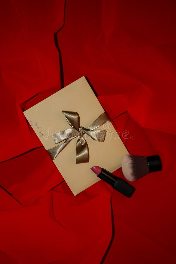 Valentine`s Day gift craft envelope with golden ribbon and sign `for you` on red background. Valentine`s Day Gift. Craft paper envelope with a handwrite sign ` stock images