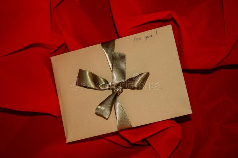 Valentine`s Day gift craft envelope with golden ribbon and sign `for you` on red background. Valentine`s Day Gift. Craft paper envelope with a handwrite sign ` royalty free stock images