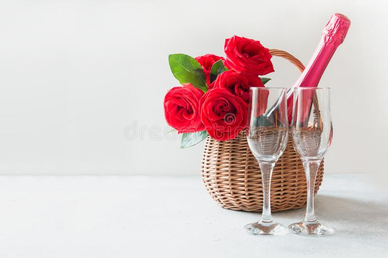 Valentine`s day gift hamper, bouquet of red roses, champagne and wineglasses on white. Valentine`s day gift hamper, bouquet of red roses, champagne, and stock photography