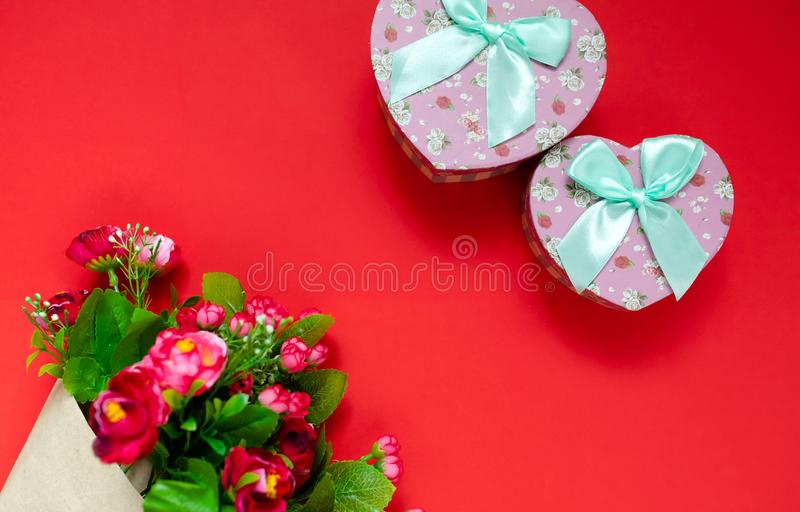 Valentine`s day gift for the second half, a bouquet of flowers, a romantic photo, a cardboard pink heart bow on a red background, stock photo