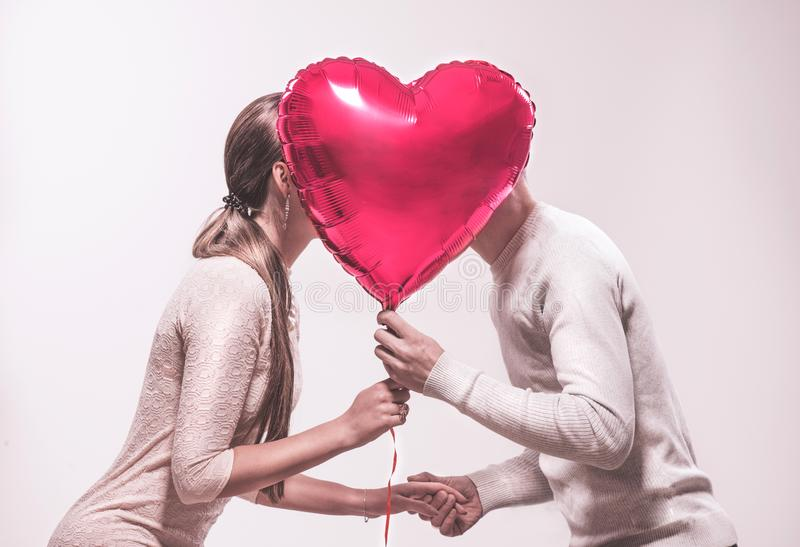 Valentine`s day. Happy joyful couple holding heart shaped air balloon and kissing. Love. Happy Valentine`s Day royalty free stock images