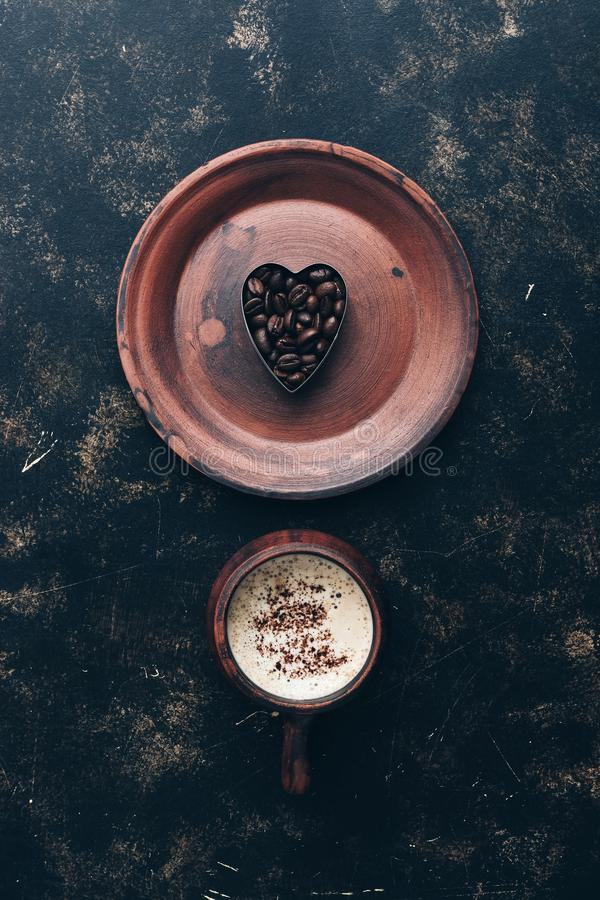 Valentine`s Day. Heart of coffee beans and hot coffee drink in a vintage cup on a rustic dark background. Top view, place for tex stock photos