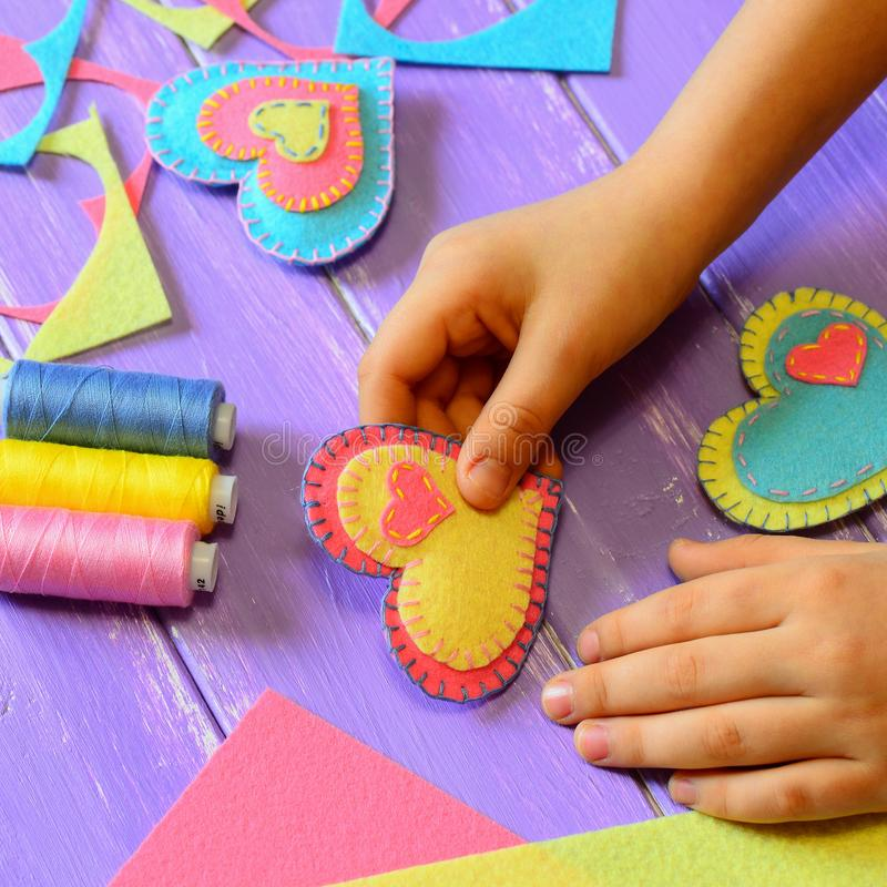 Child holds a felt heart ornament in his hand. Child made a heart ornament. Felt hearts, tread set, felt sheets and pieces. Valentine`s Day heart crafts for kids royalty free stock image