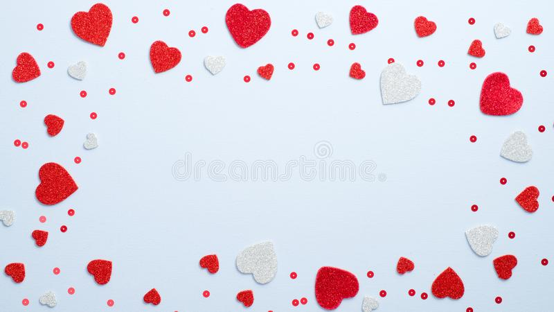 Valentine`s Day holiday frame made of red and white hearts on blue background. Romantic greeting card mockup. Love concept royalty free stock photos