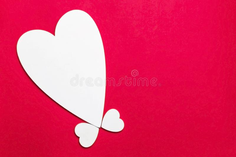 Valentine`s day holiday, mother`s day, March 8, wedding invitation. Symbol of love white wooden heart on a red background with royalty free stock photography