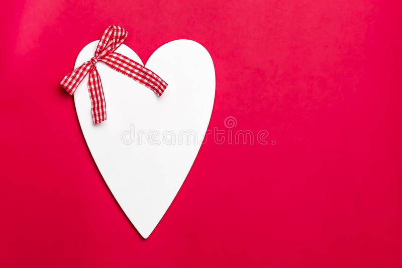 Valentine`s day holiday, mother`s day, March 8, wedding invitation. Symbol of love white wooden heart on a red background with royalty free stock photos