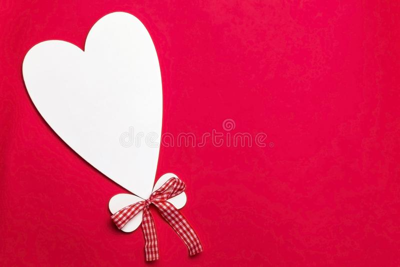 Valentine`s day holiday, mother`s day, March 8, wedding invitation. Symbol of love white wooden heart on a red background with royalty free stock photo