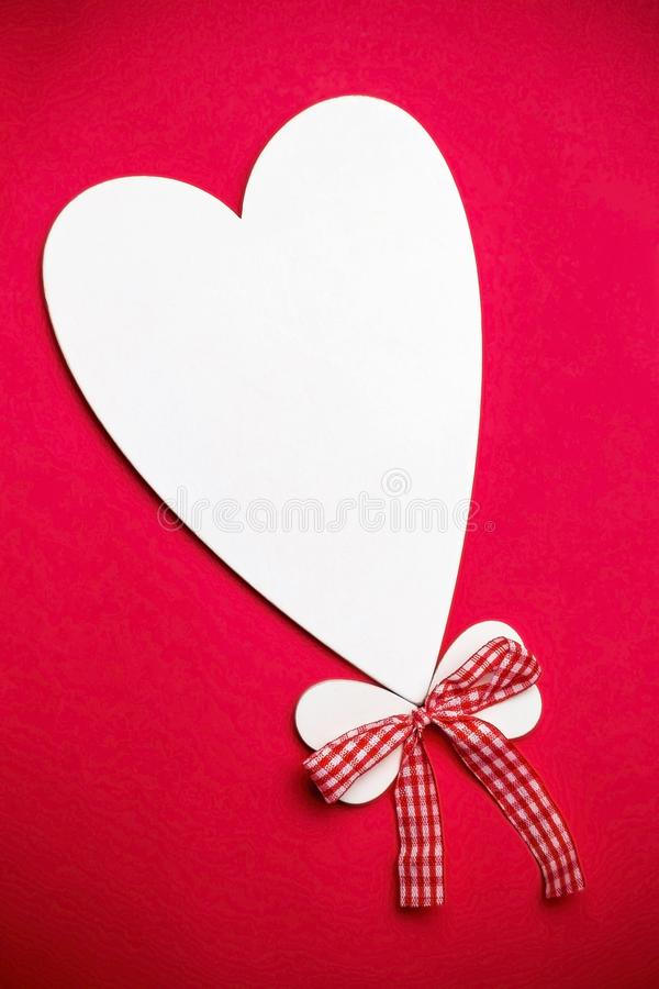 Valentine`s day holiday, mother`s day, March 8, wedding invitation. Symbol of love white wooden heart on a red background with royalty free stock images