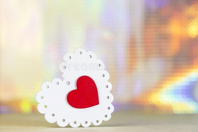 Valentine`s day holiday. Symbol of love white tracery and red purple color wooden heart on a brilliant shining abstract backgroun stock photo