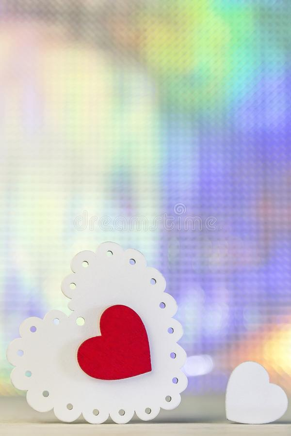 Valentine`s day holiday. Symbol of love white tracery and red purple color wooden heart on a brilliant shining abstract backgroun royalty free stock images