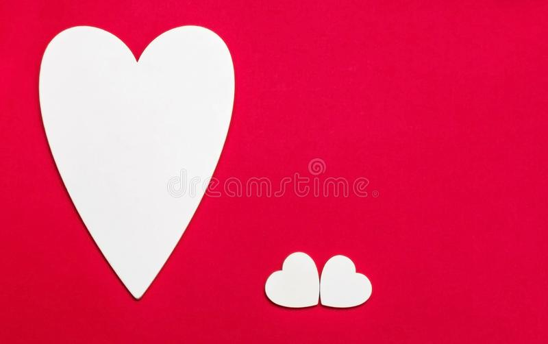 Valentine`s day holiday, wedding invitation. Symbol of love white wooden heart on a red background with empty space for text royalty free stock photography