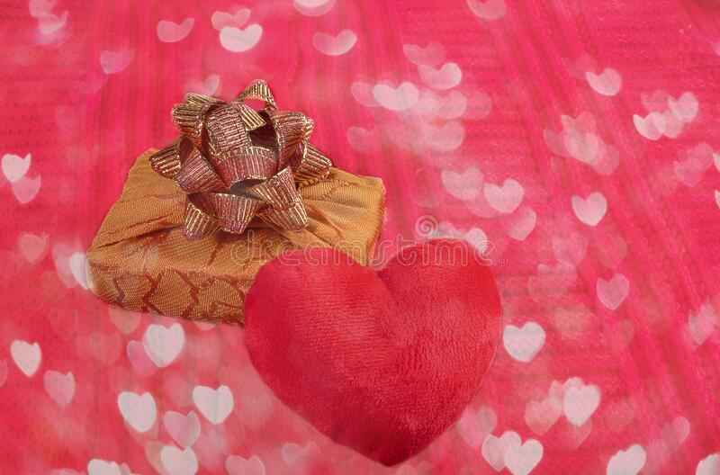 Valentine`s day homely cosy background. Close-up plush heart and gift box on red knitted canvas with hearts bokeh. Valentine`s day homely cosy background. Red stock image