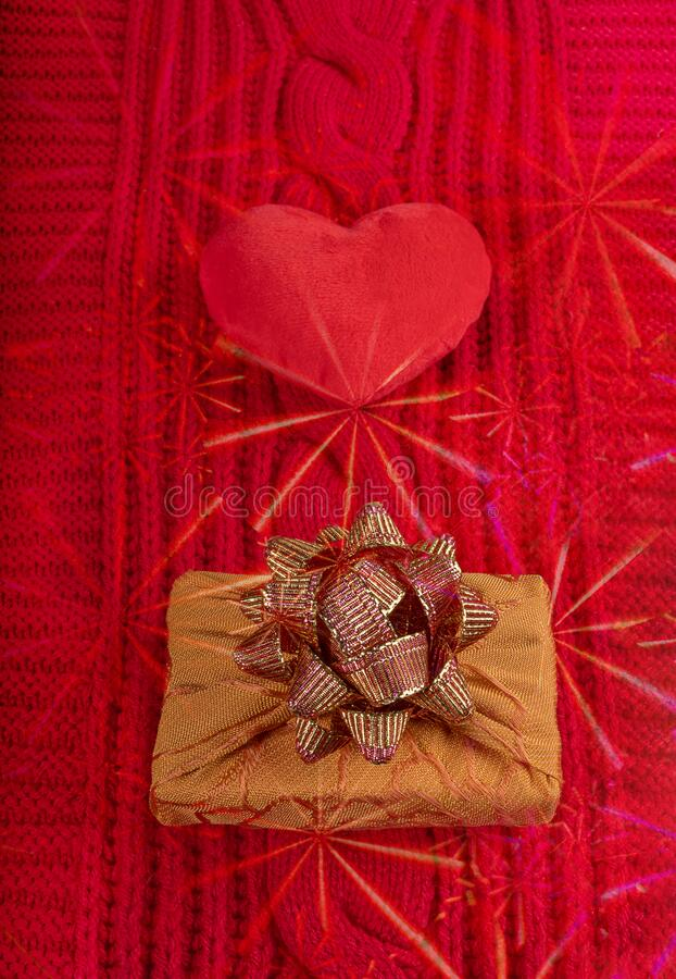 Valentine`s day homely cosy background. Plush heart and wrapped gift box on red knitted cloth with asterisks overlay. Valentine`s day homely cosy background stock image