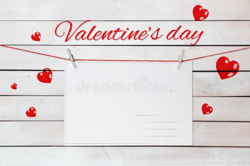 Valentine`s day lettering and postcards on red threads surrounded by hearts on wooden white background stock image