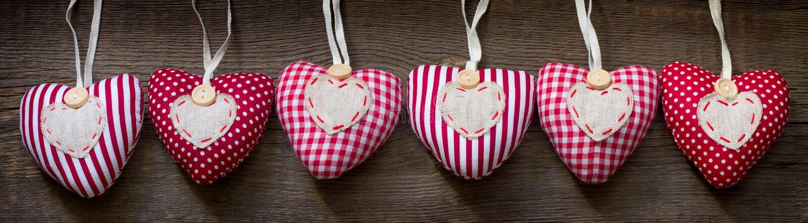 Valentine`s day love fabric homemade hearts banner concept on old vintage wooden retro background. Closeup stock photography
