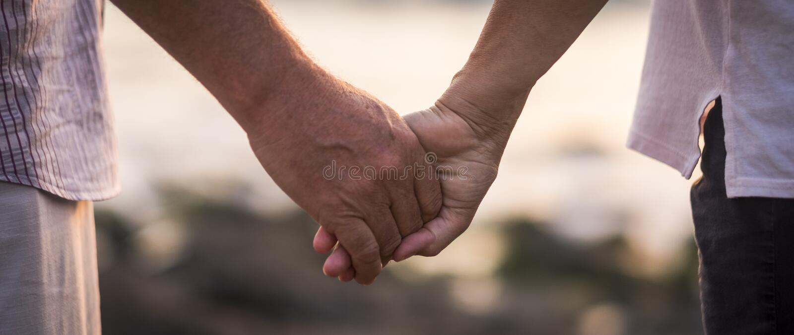 Valentine`s day love over time concept with hands of man and woman mature old people aged taking together each other with royalty free stock photography