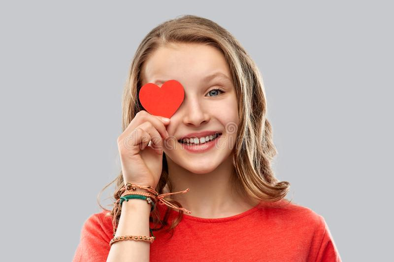 Smiling teenage girl covering eye with red heart stock photo