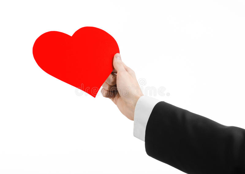 Valentine's Day and love theme: a man in a black suit holding a red heart isolated on a white background. In studio royalty free stock photos
