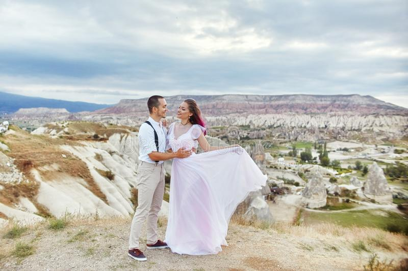 Valentine`s day loving couple in nature hugs and kisses, man and woman love each other. Mountains of Cappadocia in Turkey royalty free stock images