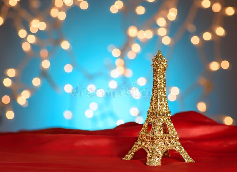 Valentine`s Day in Paris. Christmas, New Year in Paris. Golden Eiffel Tower on bright red satin. Blurred Xmas lights background. royalty free stock photography