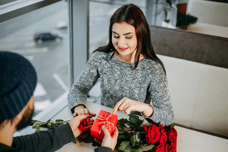 Valentine`s day present. Man presenting a gift and flowers to hi royalty free stock images