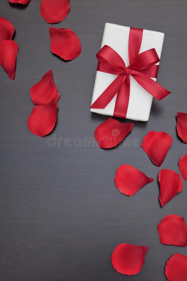Valentine`s day present with red rose petals. stock images