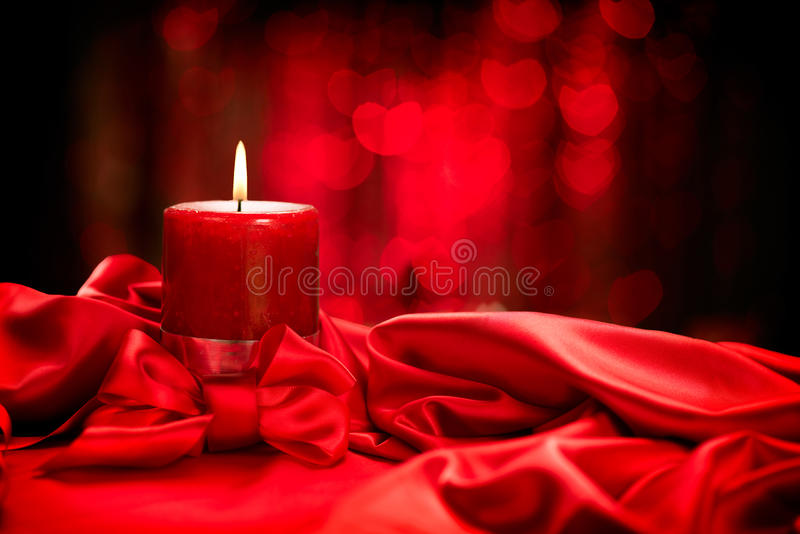 Valentine's Day. Red candle on red silk stock image