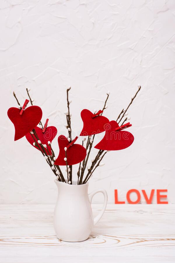 Valentine`s Day. Red felt hearts on willow branches in a white jug on the table stock photography