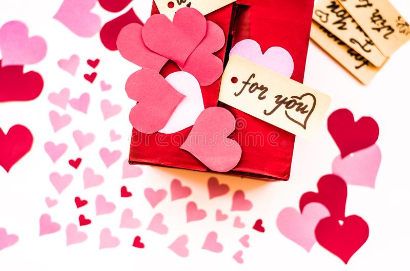 Valentine`s day red gift box with a gap for paper valentines. Valentine`s day holiday. red box for valentines with paper hearts. valentine messages and gift stock photos