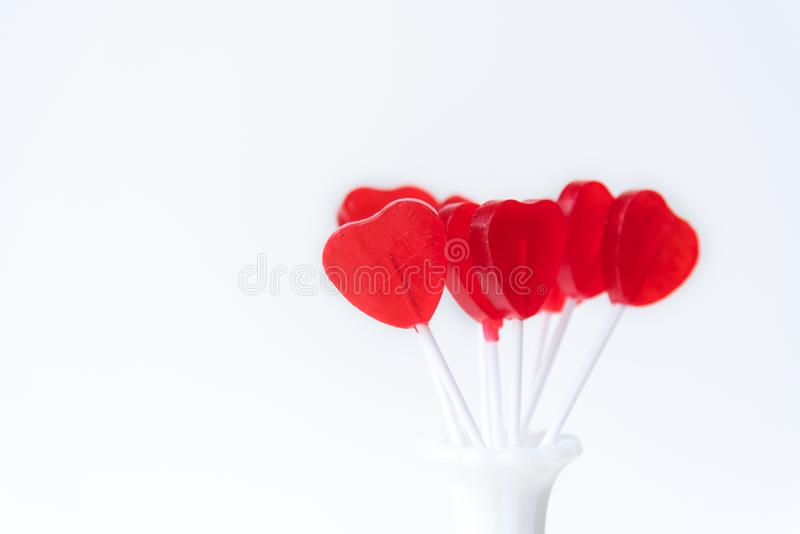 Handful of red heart shaped lollipops standing in white vintage vase with white background stock photography